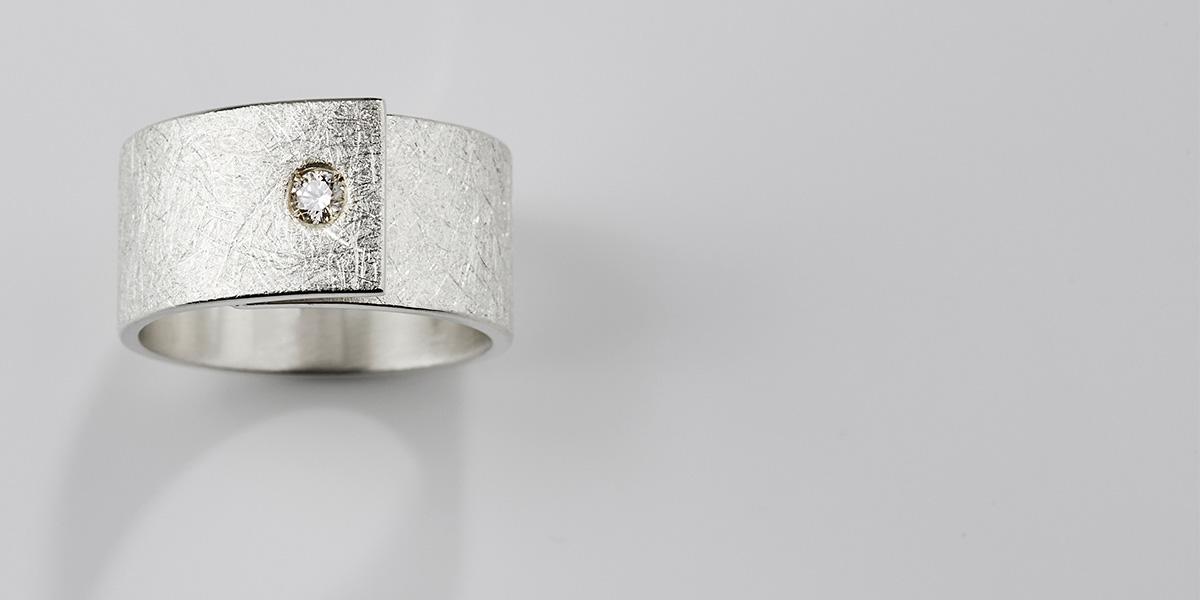 Unieke witgouden trouwring met structuur en witte diamant