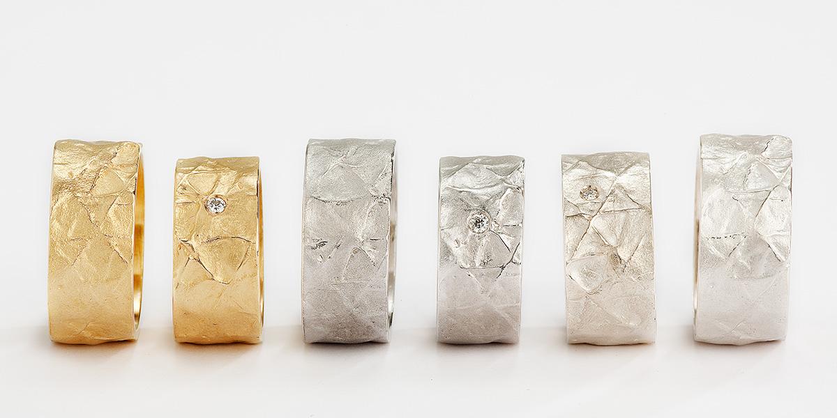 Handgemaakte trouwringen in verschillende tinten 18k goud met textuur en witte diamant