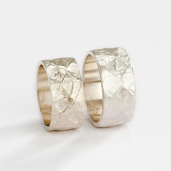 Handgemaakte trouwringen in 18k witgoud met textuur en witte diamant