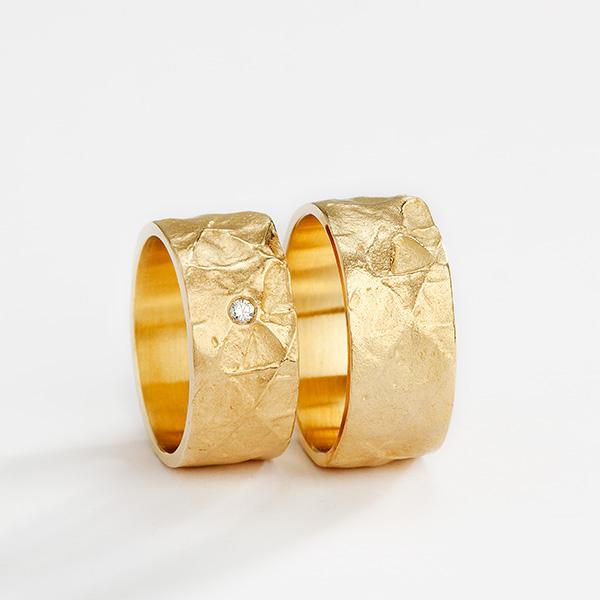 Handgemaakte trouwringen in 18k geelgoud met textuur en witte diamant